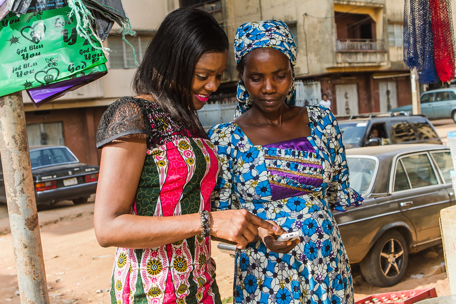 At a surprise visit to Ifeoma's business, she scrolls through her phone showing YTF's CEO, Njideka Harry, the business and educational related text messages she receives from YTF weekly, helping her to keep focused on growing her business, supporting her family and impacting her community, for good.