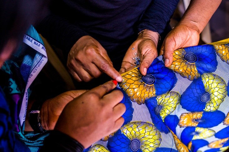 Charity and her two female apprentices embellishing fabrics with beautiful beads.