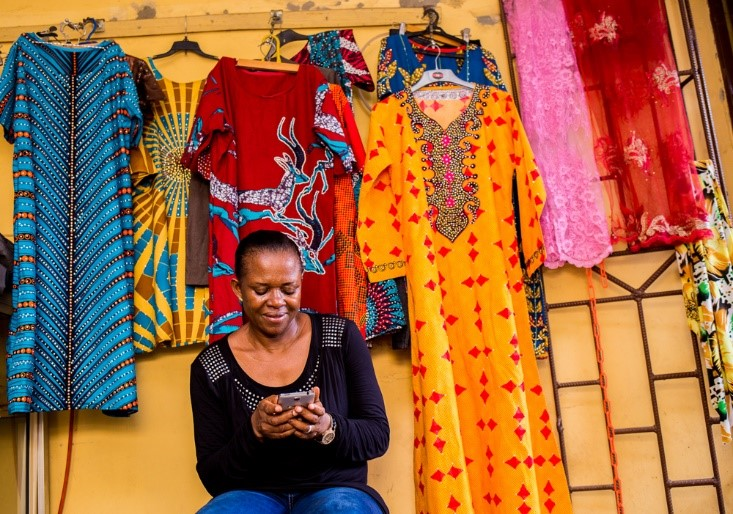 Mobile-focused Charity at her shop Fanchi Global Resources, with her garments making a colorful backdrop.