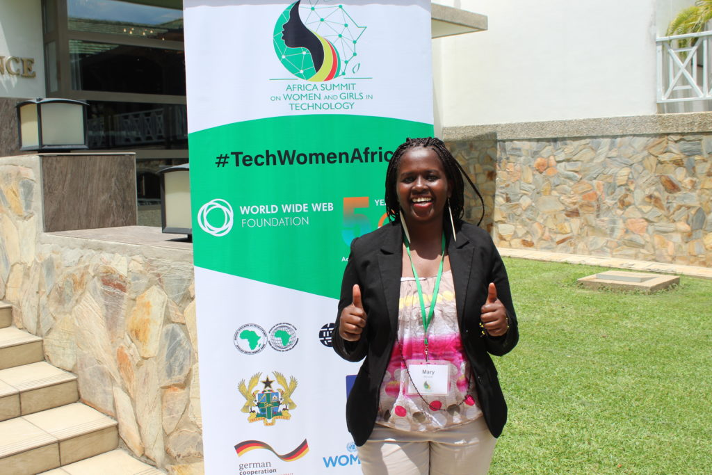A dark-skinned African woman in professional dress giving double a double thumbs up standing in from of a sign reading #TechWomenAfrica at the Africa Summit for Women and Girls in Technology in Ghana.