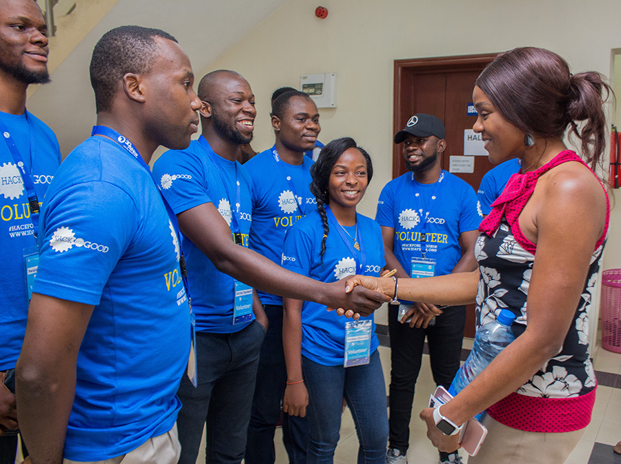 A group of smiling, dark-skinned young men and women in matching blue t-shirts gather around a well-dressed dark-skinned business woman. One young man shakes hands with the business woman.