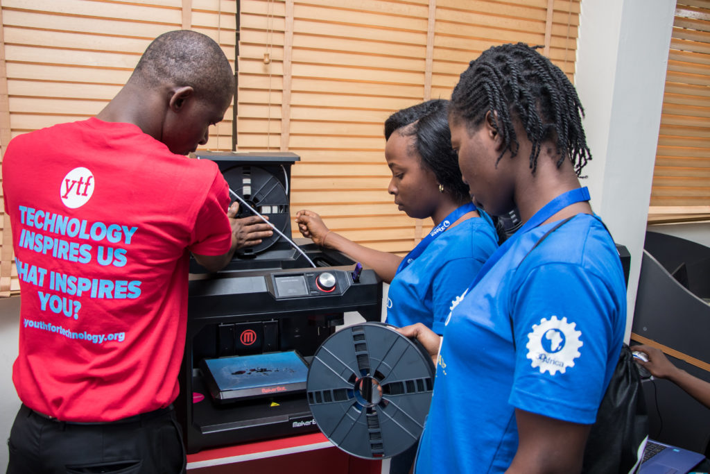 A dark-skinned male instructor demonstrates to two dark-skinned girls how to change the filament spool on a 3D printing machine.