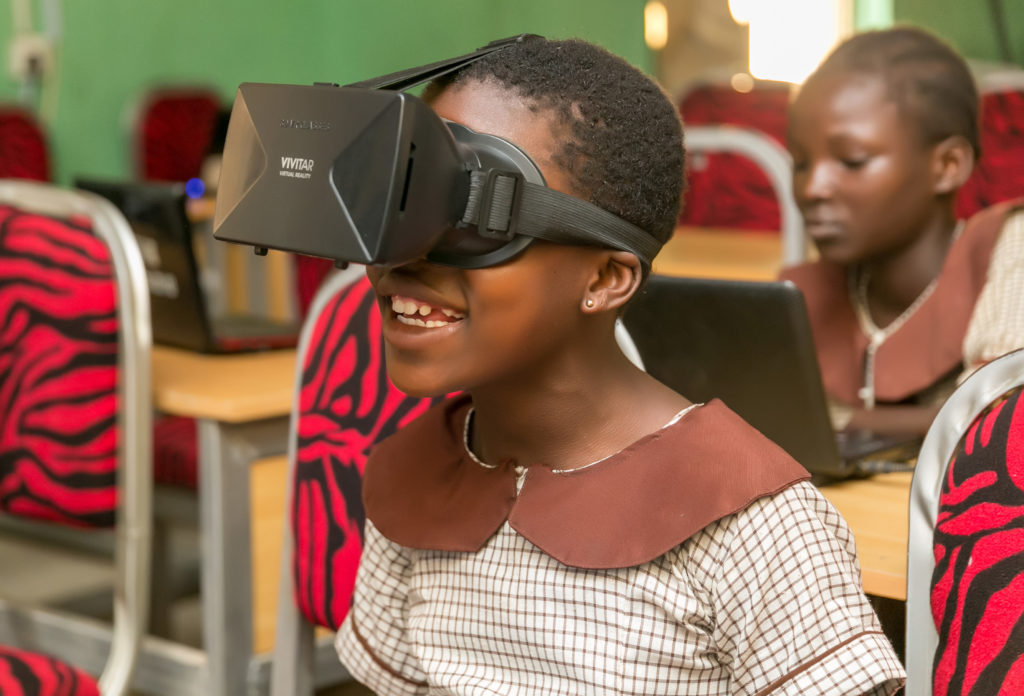 A dark-skinned girl in a brown school uniform wears a virtual reality headset while another dark-skinned girl in same uniform works on laptops in the background.