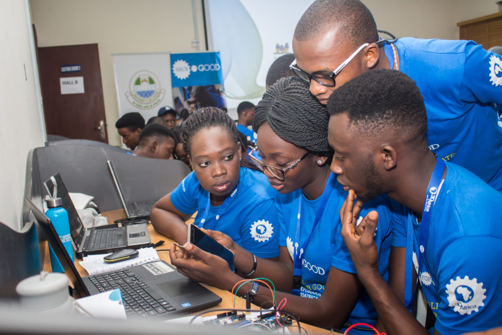 Two dark-skinned women and two dark-skinned men in matching blue 3D Africa t-shirts examine a smartphone at a worktable with laptops and exposed circuits on top.