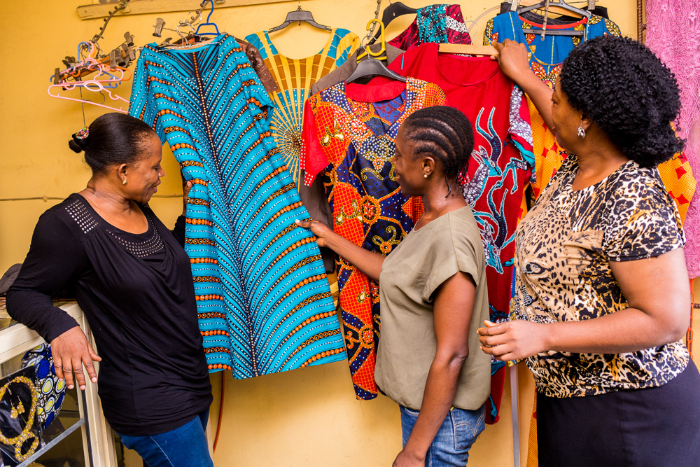 Three dark-skinned women admire brightly colored dresses hanging on a display