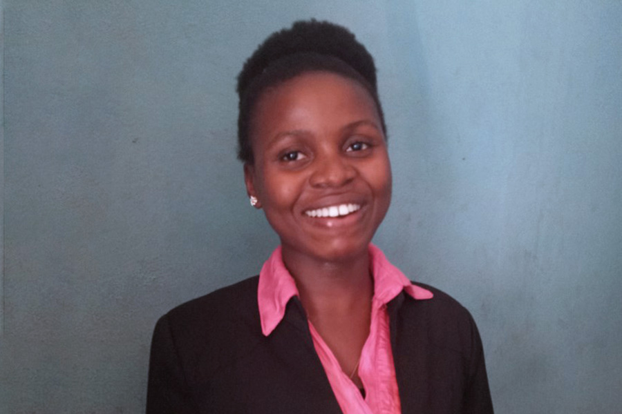 A dark-snikked woman with short natural hair in a professional pink button-up shirt and black blazer smiles.