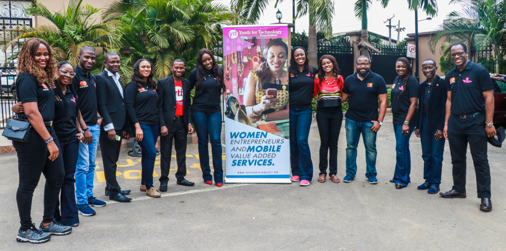 A group of dark-skinned men and women, some wearing polo shirts embroidered with the Mastercard logo, some wearing Youth for Technology Foundation shirts, gather around a banner that reads Women Entrepreneurship and Mobile Value Added Services